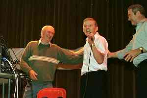 Sean Dempsey (left) received a tribute in song from his friend, Ted Twomey, at last year's Manchester International Set Dancing Festival. Donncha Ó Múinneacháin is also on stage.